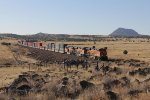 Picacho Butte stands tall in the distance as three C4's take another intermodal west