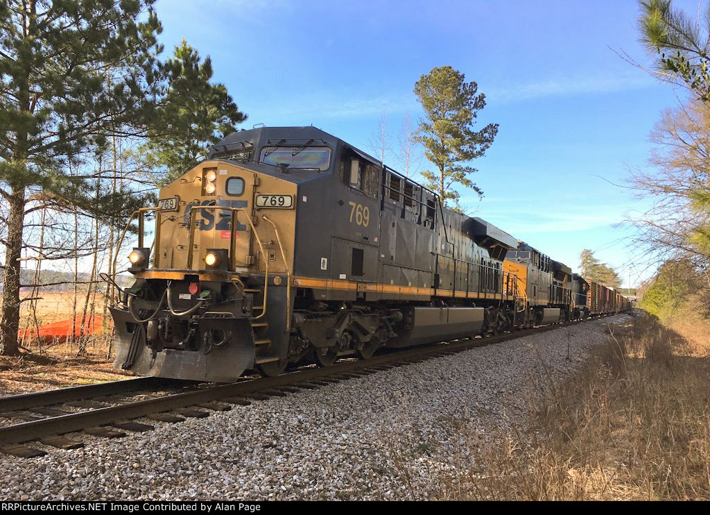 CSX 769, 3409, and 2736 pause with a line of boxcars