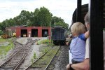 Passengers of all ages look around as the tour train passes the shop area