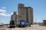 Two Geeps pose in front of some Grain Elevators