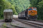 BNSF 3740 shoves its grain train past a cut of sand hoppers waiting for their next load