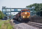 A westbound manifest charges through the Coon Rapids-Riverdale Station