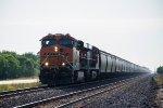 A BNSF grain train heads east in the seeing sun