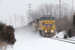 Q329 kicks up some loose snow as it comes west