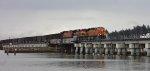 BNSF/KCS power S/B across the Mud Bay Crossing with empty coal gondolas