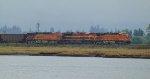 BNSF/KCS power leading an empty coal train through Mud Bay Crossing