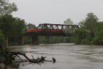 In the middle of a thunder storm, empty grain train GBVKC rolls north over the Illinois River