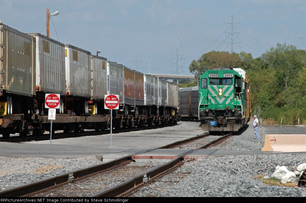 Westbound vehicle train prepares to depart Centennial Yard as an eastbound pig train passes