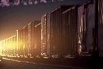 Locomotive headlight shining off boxcars