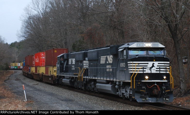 NS 22V makes approaches the grade crossing on a dreary day