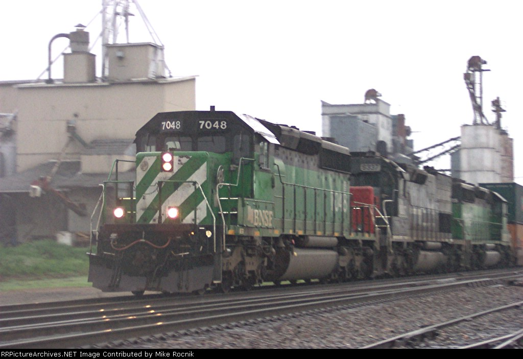 BNSF 7048 sprints through the Xovers at Wadena in a lite rainfall