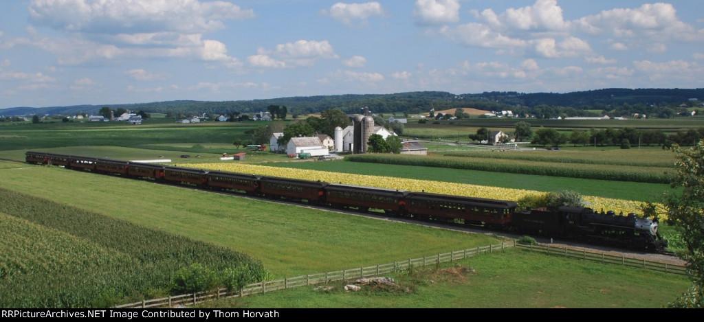 Strasburg 475 leads its nine coach consist back home thru farm fields