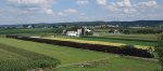 Strasburg 475 leads its nine coach consist back home thru farm fields