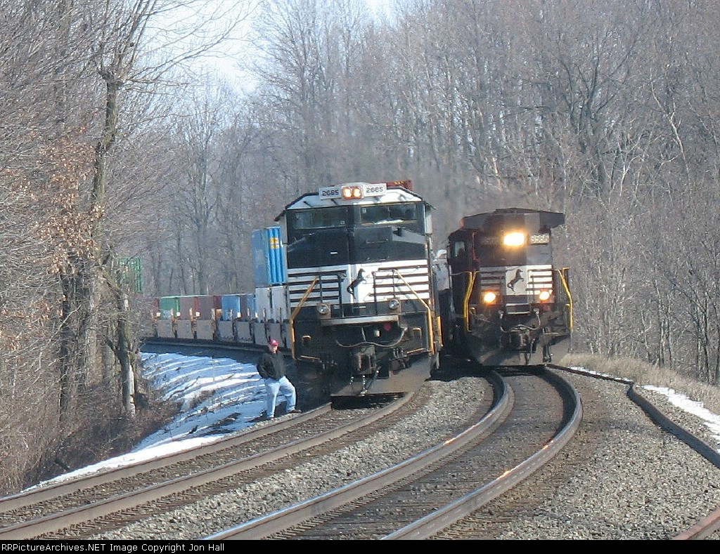 NS 8566 leading a short steel coil train past a parked container train with 2685