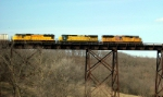 CNW 8564 helps on a EB stack train rolling onto the Kate Shelley High Bridge