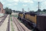 1058-10 Eastbound C&NW freight passes site of recent Burdick #1 and #2 grain elevator fire next to MILW Bass Lake Yard