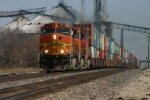 The massive grain complex towers over BNSF 4654 west
