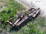 Rail Sections Used for Some Type of Grader Sit by the Tracks