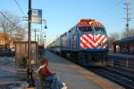 A pair of kids observe passing of a Metra train