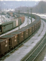 1389-15 Eastbound BN ore train passes MILW Pigs Eye Yard