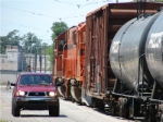 Short South Shore freight heads west as vehicular traffic passes carefully by