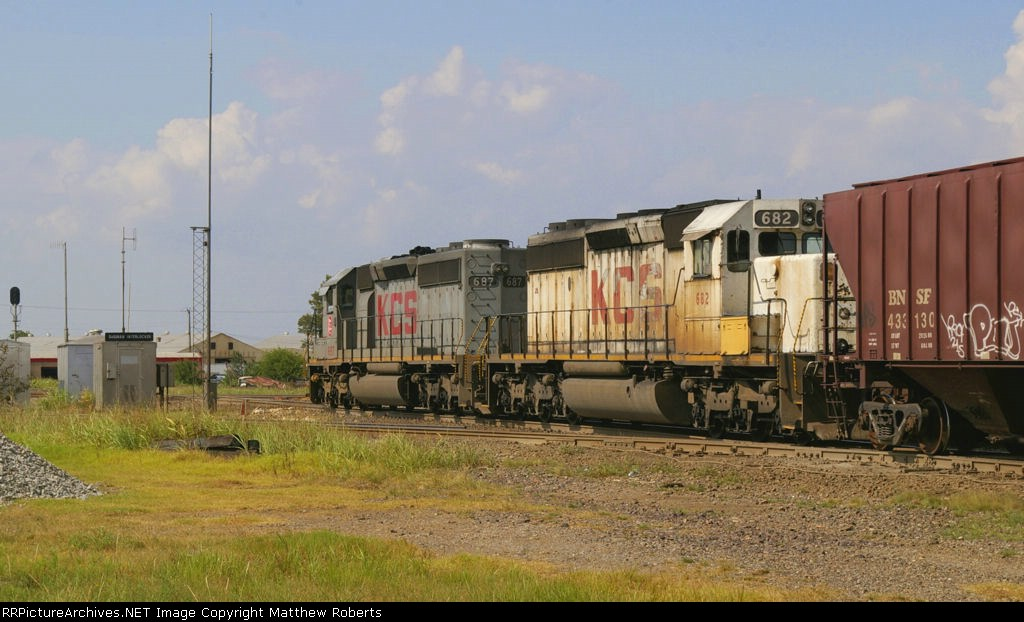 Two KCS SD40-2s (one in ghost colors) lead a grain train north on the Ft. Worth Subdivision
