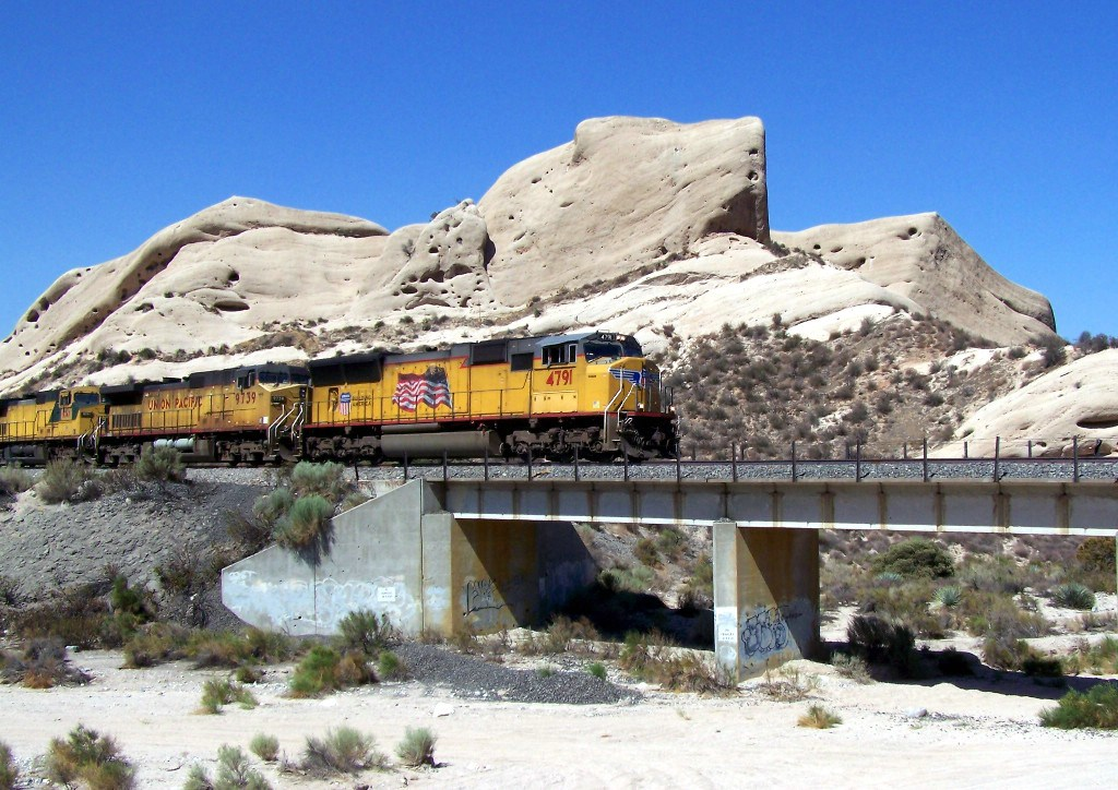 UP 4791 approaches the bridge on track 3 over the wash, in front of wind-eroded rock formations.