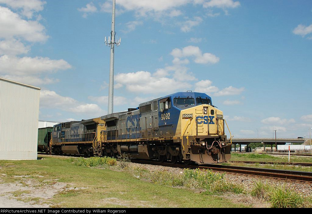 A Southbound CSX Transportation Mixed Freight Train, with GE C44-9W No. 9002 and C40-8W No. 7689 providing power, rounds a bend