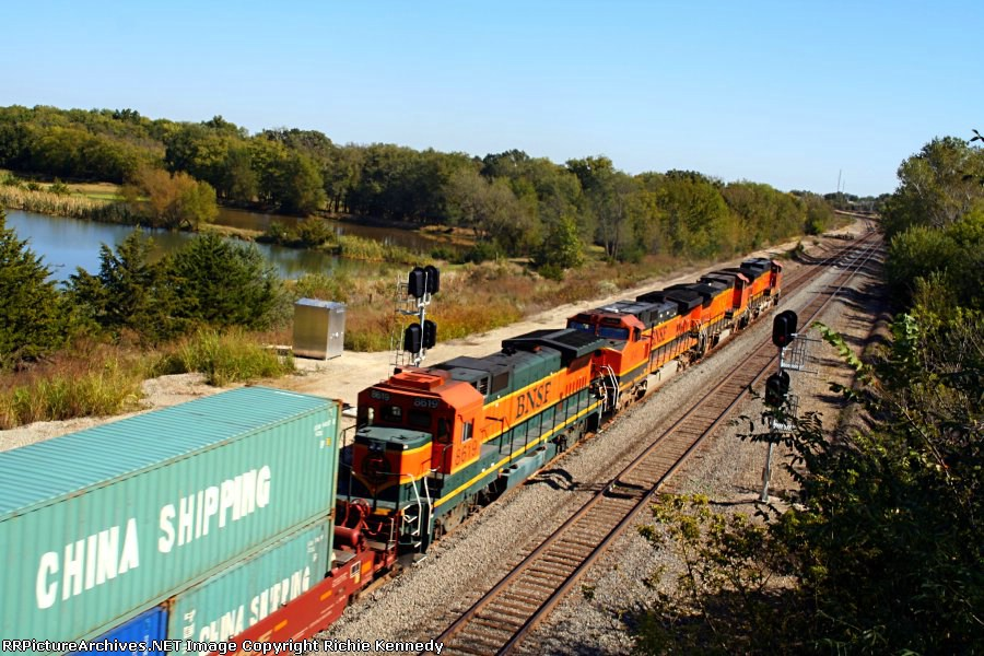 A quartet of BNSF engines, trailed by B40-8 8619, roll past the pond east of the Eisenhower Terrace Bridge.