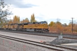 A UP coal train gos past the UTA Front Runner station on a Partly cloudy day