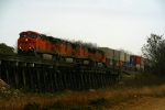 BNSF ES44DC 7638 leads C44-9Ws 5352, 4530, and 4358 on an westbound stack train across a wood trestle west of Pomona.