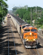 BNSF 6128 leads eastbound coal loads as a Metra equipment move overtakes it