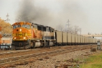 BNSF 8877 heads west with empty CEFX hoppers for PRB.