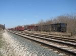 Lines of stored boxcars sit in the storage yard as E945 comes down the siding