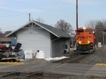 E945 rolls past the old depot, now used as a MOW building