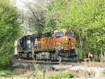Helper units on C&W V92's grain train disappear into the beautiful spring foliage