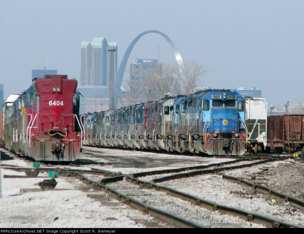 A long line of Helm engines with the Gateway Arch in the background
