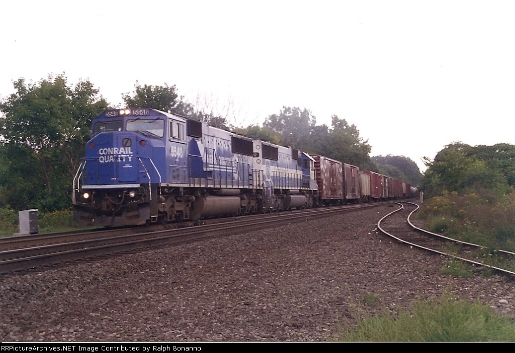 A westbound freight led by SD60M 5548 and an Oakway SD60 is about to roll across the D&H diamond