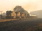 As the sun rises, a three-pack of UP SD70M's leads 33V out of the fog