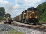 V771 heads east with coal loads past some MOW equipment