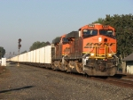 Orange BNSF power and aluminium coal cars shine in the morning sun