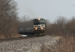 Westbound covered hoppers grumble their way slowly through the woods awaiting a meet with a tardy Eastbound