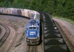 Twin Conrail SD-40-2s push a grain train eastbound while coal loads wait to go down the hill next