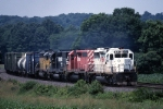 Four SD-40s of various color are heading eastbound thru the farmland
