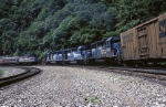 "Three Conrail EMD SD-40-2's are climbing uphill with mixed tonnage while the Amtrak ""Pennsylvanian"" drifts downhill"