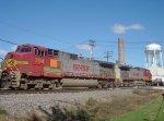Two Warbonnet Dash 9s trail behind two in differing orange schemes