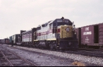 Erie-Lackawanna EMD GP-35 2563 and an EMD F-7B arrive in the yard with a mixed freight
