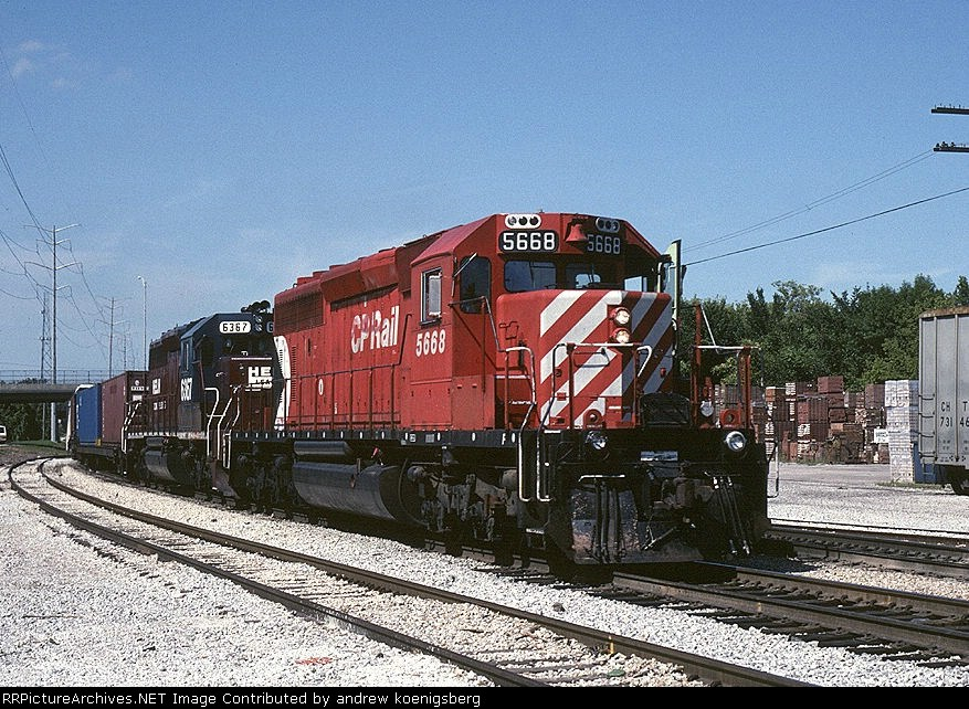 Canadian Pacific SD-40-2 5668 and a Helm leaser wait at a signal with  a short container train