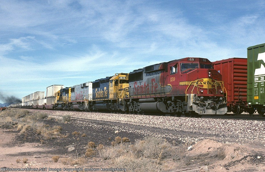 Atchison, Topeka & Santa Fe EMD GP-60M 159 is passing a mixed freight on the desert
