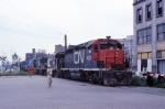 A crossing watchman guides Canadian National GP-40 4008 and three Conrail U-25-B's across the street